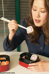 An Asian American Woman is eating Sushi with Chopsticks from a take-out container in her office. She is holding a piece of sushi with her chop sticks bringing up to her mouth.