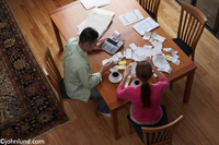 A young couple sit at their dining room table with receipts and an adding machine dealing with thier finances. In addition to the paperwork they have cups of black coffee.