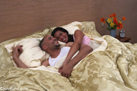 A Happy African American couple show affection in bed together in their bedroom. She has her arms around him and they are under a gold colored comforter. Fresh flowers are on the nightstand.
