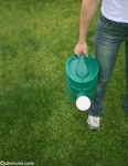 A man is holding a watering can and standing on green grass symbolizing environmental issues. The man has on blue jeans and a t-shirt with white sneakers.