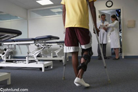 In the foreground a man on crutches waits while two doctors discuss his medical case. The man is facing away from the camera and is visible from the shoulders down.