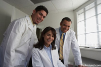 Three doctors together in an office look towards the camera. Picture of doctors in an office. Medical photos for advertising. The three doctors, a woman and two men, are all wearing white lab coats.