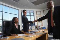 Three ethnically diverse executives meet in an office and two of them are shaking hands in this business stock photo