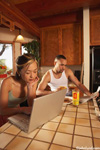 In the early morning, in the kitchen, A woman uses a laptop to check the internet while her partner reads the newspaper. The woman is using the laptop on the kitchen counter. A glass of orange juice sits nearby. The man is wearing a white t-shirt.