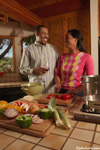 An black couple work together preparing fresh vegetables for the family dinner. She is wearing an argyle sweater and he is wearing a striped dress shirt. On a cutting board on the counter top are an array of fresh vegetables.