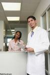 An Hispanic Doctor wears a white lab coat as he stands at his reception desk with his African American Receptionist