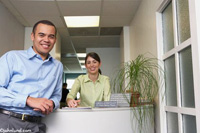 A smiling African American man stands in front of a smiling Hispanic receptionist in this medical stock photo