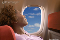Picture of woman asleep on a commercial airliner with a smile on her face as she enjoys her flight. Jet passenger asleep in her seat.