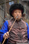 Stock photo of a tribal elder smoking his pipe in Guizhou China. The man is wearing a black fur hat and has a tunic with bright blue sleeves.