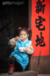 A young girl in rural China stands in a doorway an eats a bowl of rice beside a bright red banner. The young girl is wearing a bright blue dress and has red ribbons in her hair.