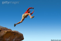 Man leaping across from a rock ledge to another ledge with the camera far below.  Man highlighted by a dark blue cloudless sky.