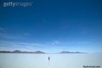 A lone man in a vast expanse of shallow water. Far off in the distance are a line of mountains and the sky is deep blue.