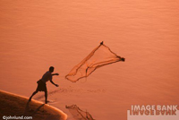 Adventure and travel stock photo of a fisherman on the Mekong River throwing out his net at sunset.
