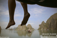 Woman's legs from below in Ha Lon. A pair of bare feet and legs are dangling over the edge of a dock. Beautiful scenic background.