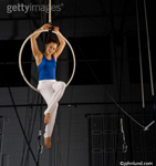 Trapeze artist sitting in a large ring high up near the ceiling. The circus performer is wearing a blue top and white pants.