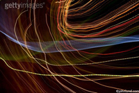 Light patterns creating with bending twisting wavy tracks of light beams wandering and wiggling around the background.