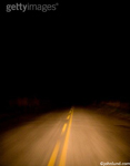 Night picture of road through sugar cane fields in Brazil shot from a moving car. This is a picture of mystery, journey and the unkown.