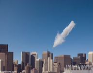 Stock photo of a cloud shaped like an arrow pointing at a high rise in a modern city in an indication of cloud computing.