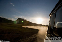 Mongolian sunset - picture of dust billowing out behind a four wheel drive Russian van as we cross Mongolia at close to sunset.