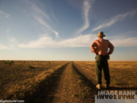 A rutted dirt road stretches into the distance as a traveler gazes out to the horizon in a stock photo shot in Mongolia.