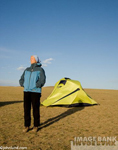 Picture of an active senior woman in Mongolia standing outside her yellow tent pitched on the Mongolian Steppes. Picture of an active,healthy, senior woman.