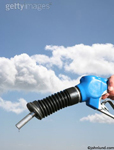 Gas nozzle to illustrate themes around energy, fuel, petrol and environmental issues. Black and blue colored gas nozzle filling the frame with a cloudy blue sky as the backdrop.