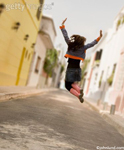Stock photo of a woman jumping for joy in an urban street, an alley in fact, in Buenos aires, Argentina.