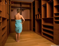 Woman standing in an empty walk-in closet wearing only a towel as she ponders her lack of apparel, clothing and shoes. The towel she has wrapped around her is blue.