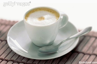 A delicious cup of cappuccino on a saucer with a spoon. White froth on top. Saucer is sitting on a bamboo mat.