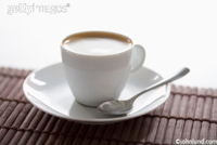 Simple latte in a cup and saucer with a spoon on a bamboo mat with an all white background.