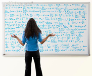 Picture of a woman deciphering a complicated math problem filling a whiteboard completely. Woman has long black hair and is wearing a blue blouse and dark pants. Woman viewed from rear.