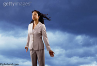 A Woman is standing facing the wind with her hair blowing in it and a dark cloudy stormy sky. The woman is Hispanic or black and is wearing a gray business suit.Her hair and clothes are being whipped by the wind.