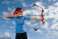 Blindfolded woman shooting an arrow blindly from a modern compound bow set against a blue but cloudy sky. Woman is wearing a blue blouse and black pants. The blindfold she is wearing is bright red.