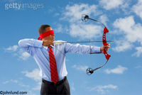 Blindfolded man shooting an arrow from a high tech compound bow. The man is wearing a dress shirt with a red necktie, a red blindfold, and slacks. Behind the man is a cloudy blue sky.