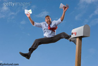 Black man jumping for joy in front of his mail box. The man is high in the air with an envelope in one hand an a letter in the other. Man with good news.