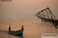 Two men are getting ready to launch their small boat at sunrise on the beach near Cochin India. The men aim to catch fish with their nets.