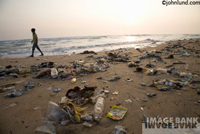 Photo of a beach awash with trash, garbage and debris at a spa on the coast of India illustrating the building environmental disaster occuring in the world's oceans.