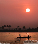 Travel photo of fisherman silhouetted against the setting sun as they throw their net from a small boat. Gorgeous beautiful sunset with a red sky and the setting sun reflected in the water.