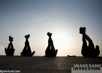 Participants of an exercise boot camp work their abs as their legs are silhouetted against a setting sun.