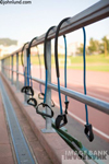 Exercise bands hang on a railing in this health and fitness stock photo. Dirt track visible in background.