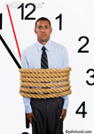 Photo of a business man tied in rope in front of a huge clock. The worker is wearing a dress shirt and tie, is black, and is tied up in time.