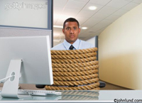 Business man at a desk tied up with rope in a comical fashion. Funny picture of an office employee tightly wrapped and tied in rope in an office cubicle.