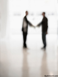 Picture of an out of focus handshake symbolizing team work, connection and agreement: A unusual business handshake.