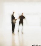 Photos of out-of-focus meeting with the participants making a connection and shaking hands. Background pictures. Abstract picture of two businessmen meeting in a hallway.