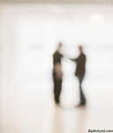 Pictures of two businessmen out of focus talking in an impromtu meeting in a well lit office lobby highly blurred.