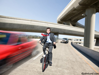 Pictures of a business man bicycling on the freeway with cars speeding by. The man riding a bike on the freeway is wearing a business suit and a red necktie, and he is in the fast lane.