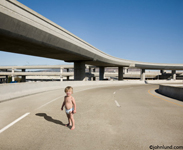 Pictures of a baby in diapers standing alone on a freeway showing risk and danger, parenting issues and political hot potatoes. Photo of a kid on the freeway.