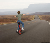 Picture of a boy riding a unicycle down a long empty road stretching through the Southwestern landscape. This is a photo of a journey, freedom and new beginnings.