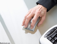 Pictures of a mature woman's hand using a computer mouse in a high-tech office setting. Close up photo of a hand on a computer mouse.