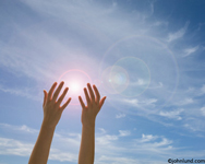 Photo of a woman's hands reaching out in front of the sun. Only the womans fore arms and hands are in the picture. It looks as though the woman is holding the sun in her hands.